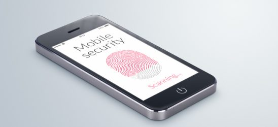 Black modern smartphone with mobile security fingerprint scanning on the screen lies on the gray surface.